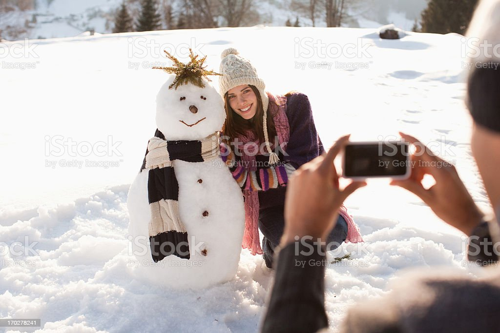 Man taking picture of girlfriend and snowman stock photo