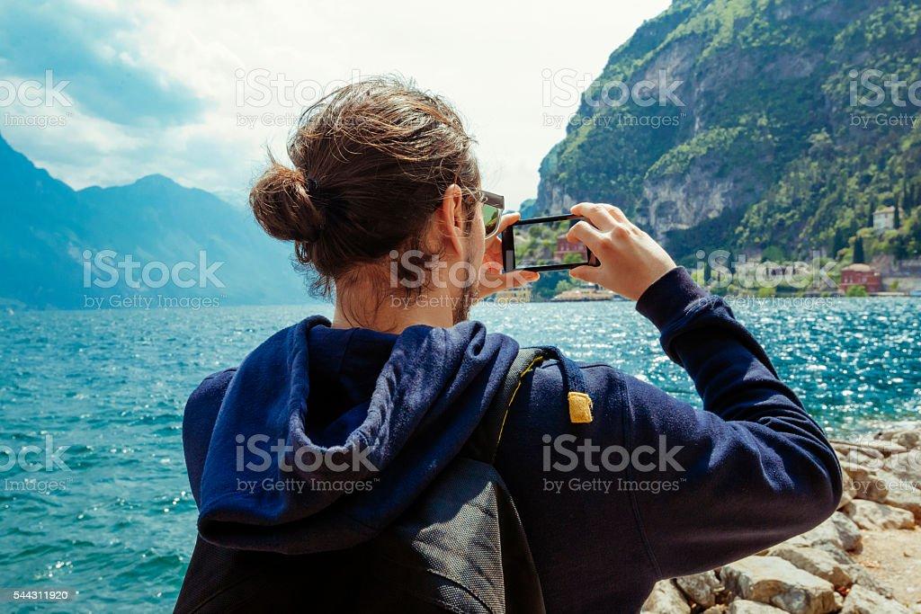 Man taking pictures on lake Garda, Italy stock photo