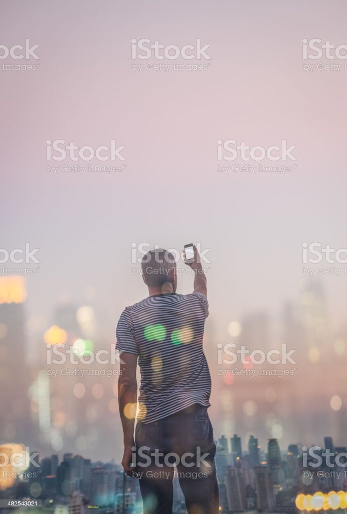 Man Taking Pictures with Smart Phone stock photo