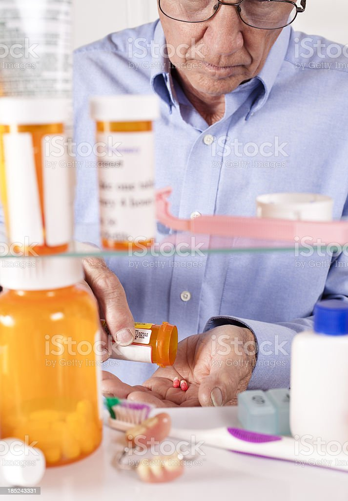 Man taking pills out of medicine cabinet royalty-free stock photo