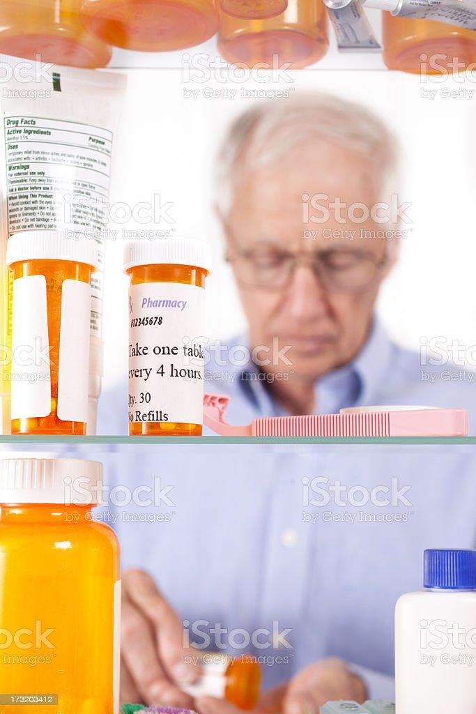 Man taking prescription pills out of medicine cabinet. Healthcare. stock photo