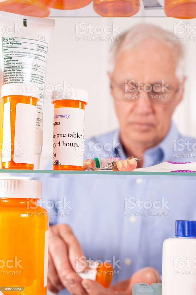 Man taking prescription pills out of medicine cabinet royalty-free stock photo
