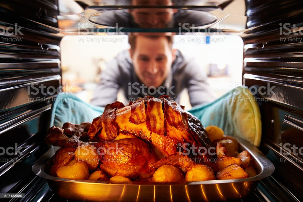 Man Taking Roast Turkey Out Of The Oven stock photo