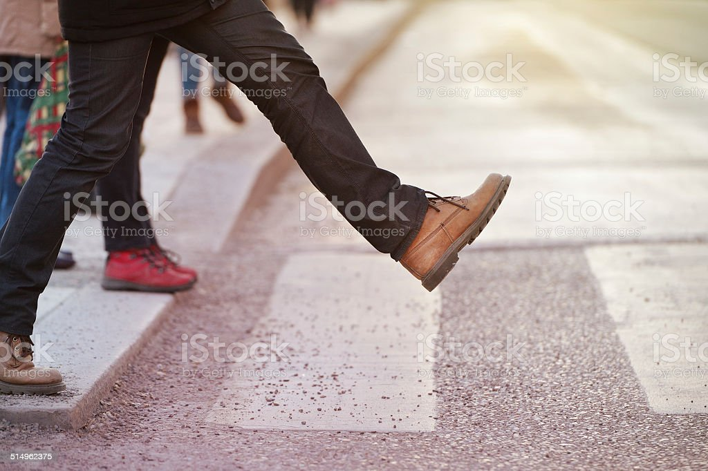 Man taking the step (onto zebra crossing) stock photo