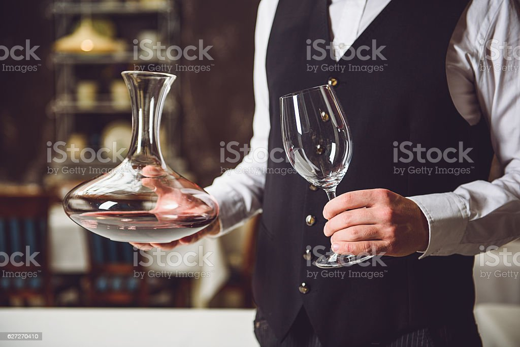Man taking vase with wine and goblet stock photo