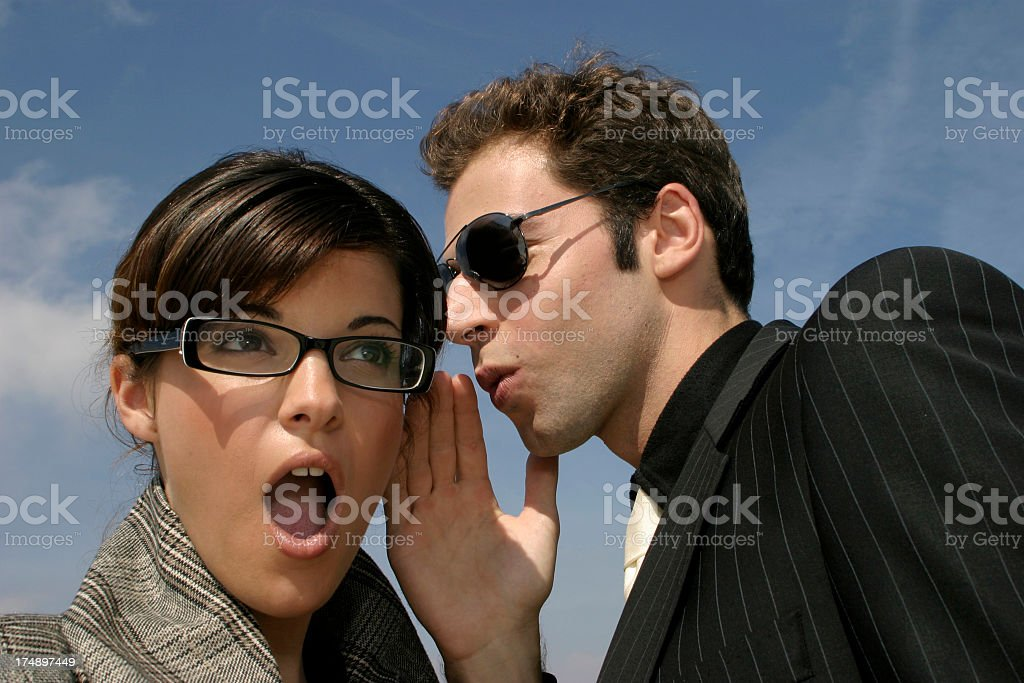 Man talking in ear of shocked woman royalty-free stock photo