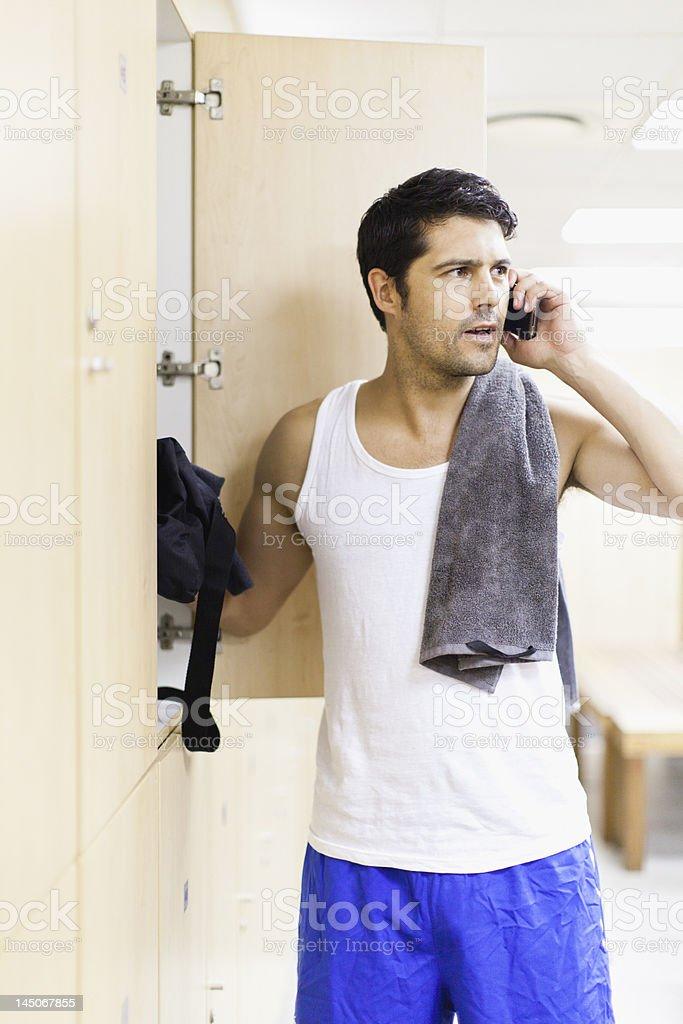 Man talking on cell phone in locker room stock photo