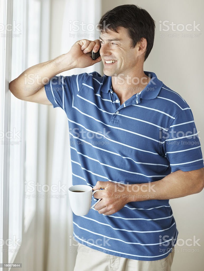 Man talking on cellphone while holding coffee cup royalty-free stock photo