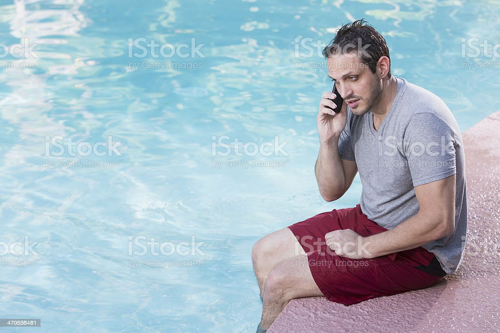 Man talking on phone by swimming pool royalty-free stock photo