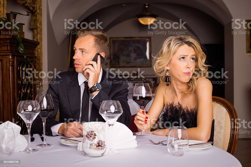 Man talking on the phone while he is on date stock photo