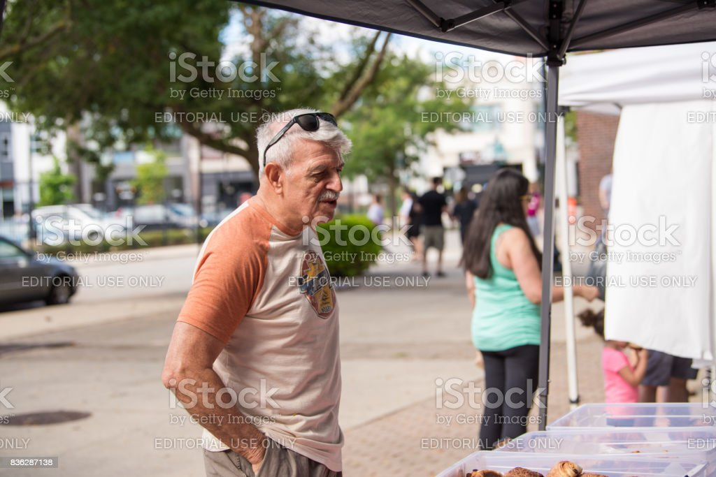 A man talking to a merchant at a local farmers market stock photo