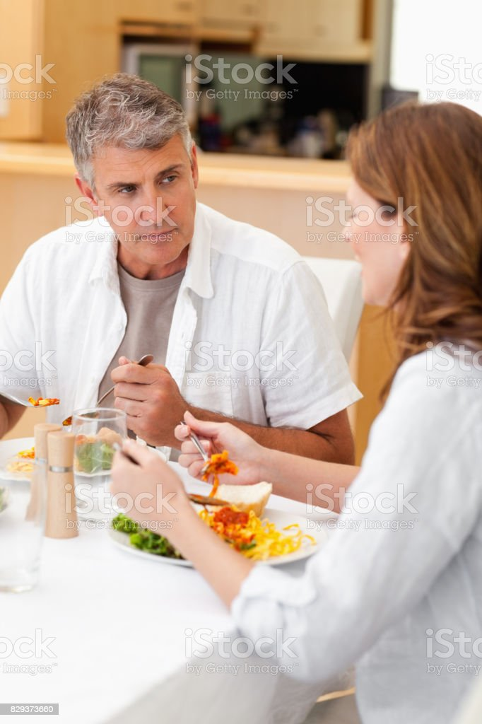Man talking to wife during dinner stock photo