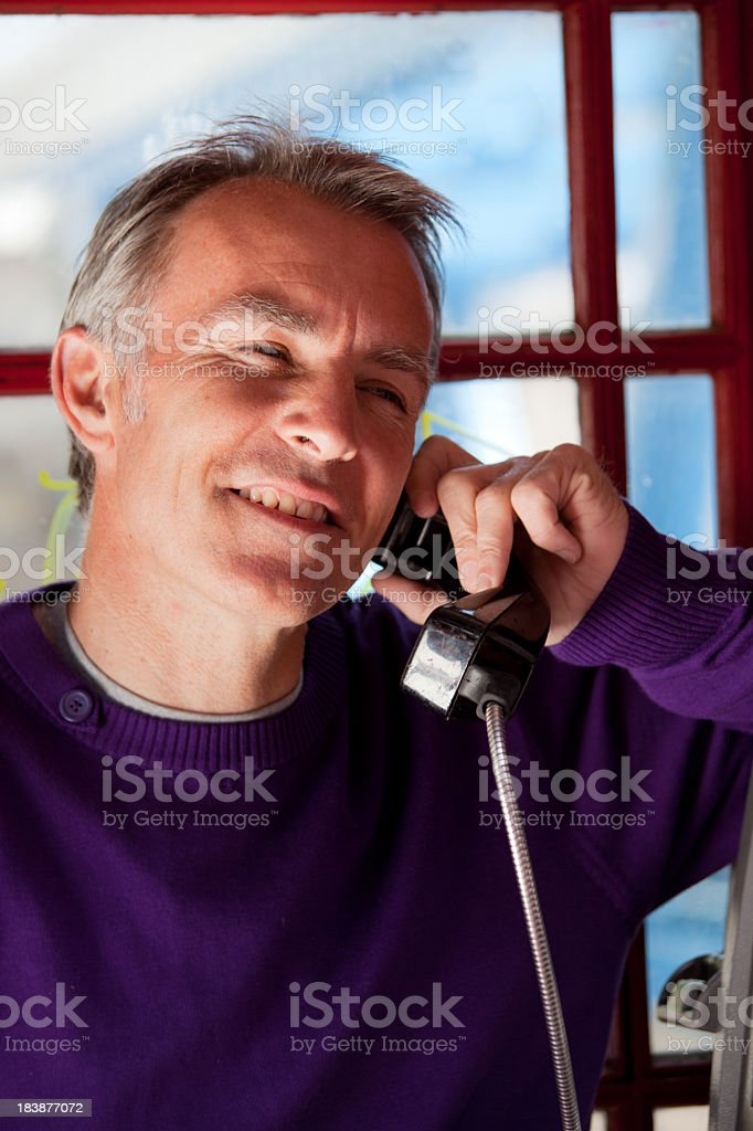 Man talks in a red london Phone booth royalty-free stock photo