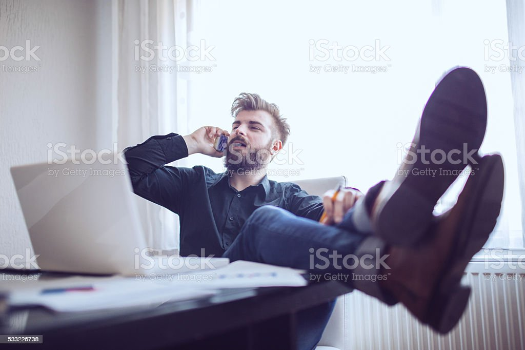 Man talks on mobile in office stock photo
