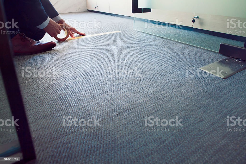 Man taping furniture lines on floor in business office stock photo