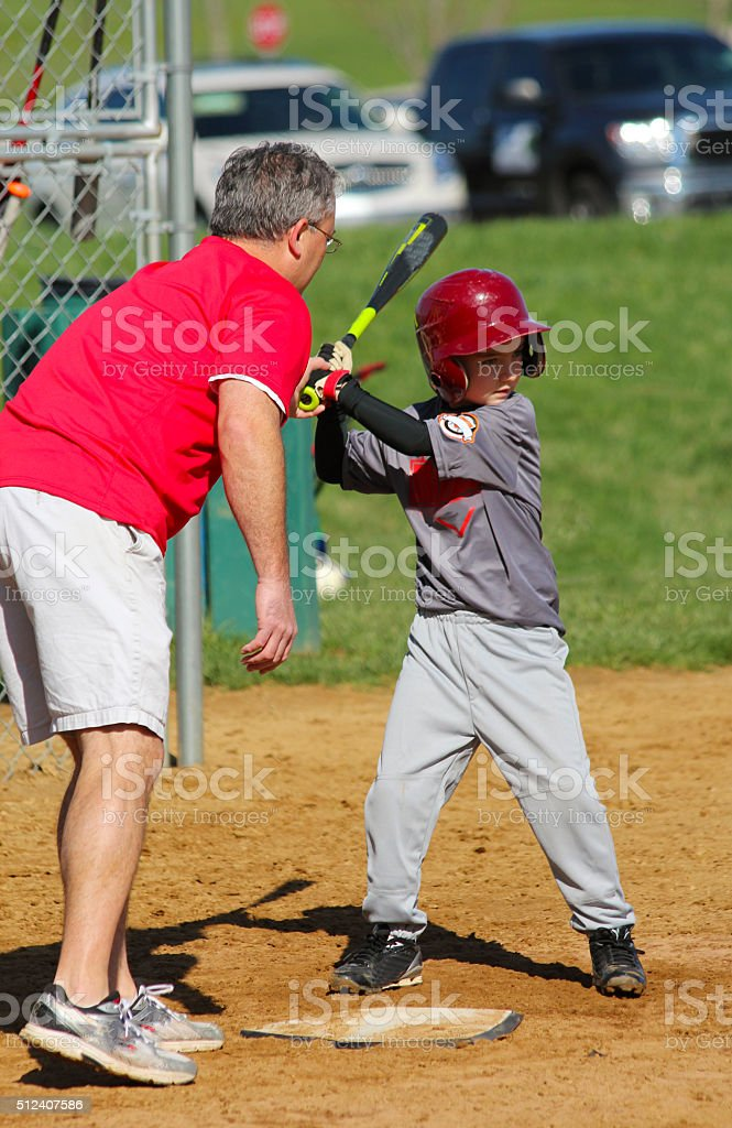 Man Teaching Boy to Hold a Bat stock photo