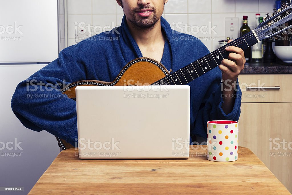 Man teaching himself to play guitar at home royalty-free stock photo