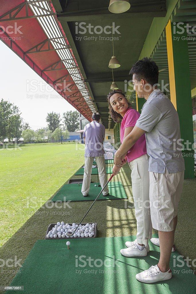 Man teaching his girlfriend how to hit golf balls royalty-free stock photo