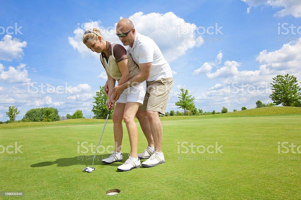 Man teaching his wife golf royalty-free stock photo