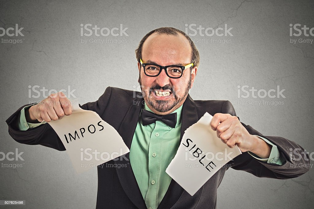 man tearing word impossible written on paper stock photo
