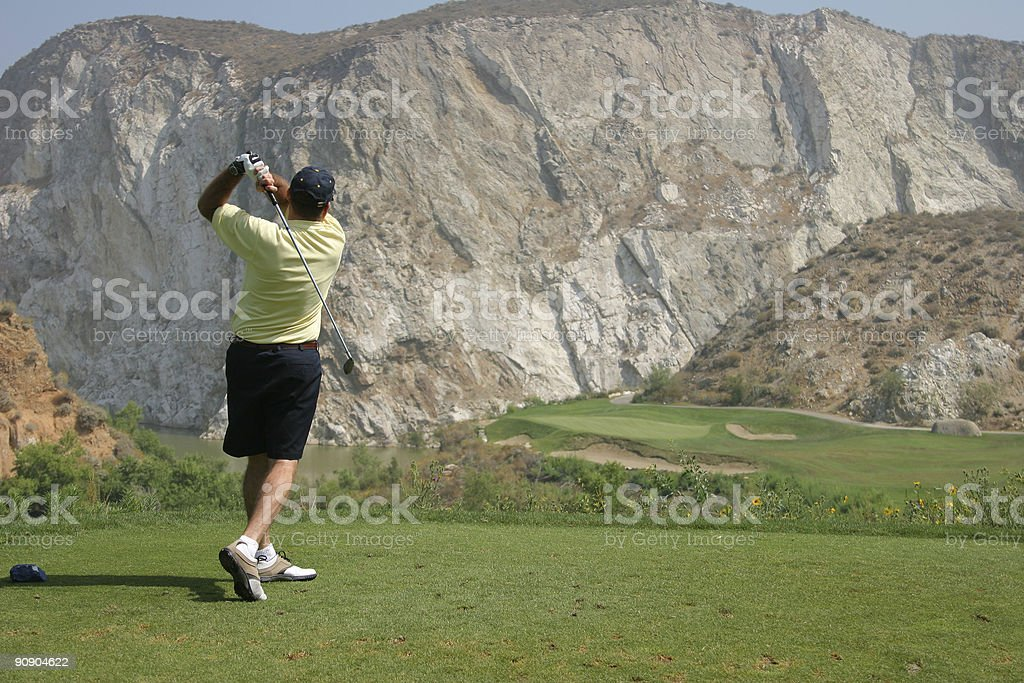 Man teeing off on a par three over water stock photo