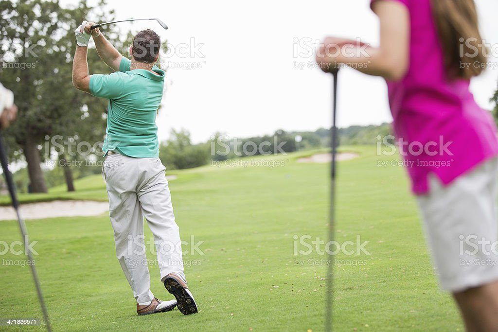 Man teeing off on golf course with family stock photo