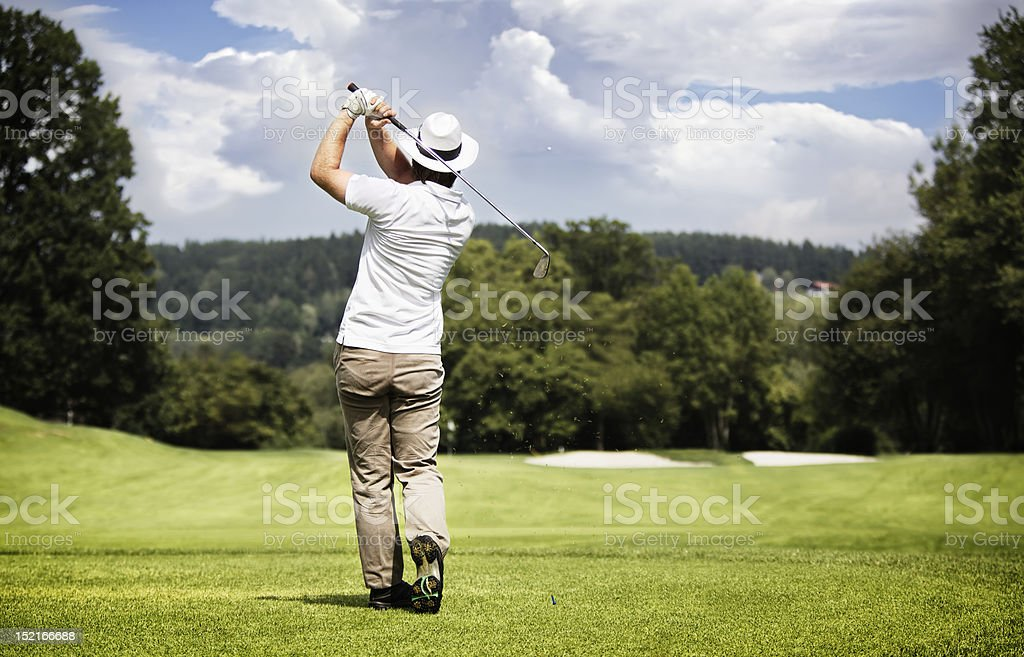 Man teeing-off golf ball. stock photo