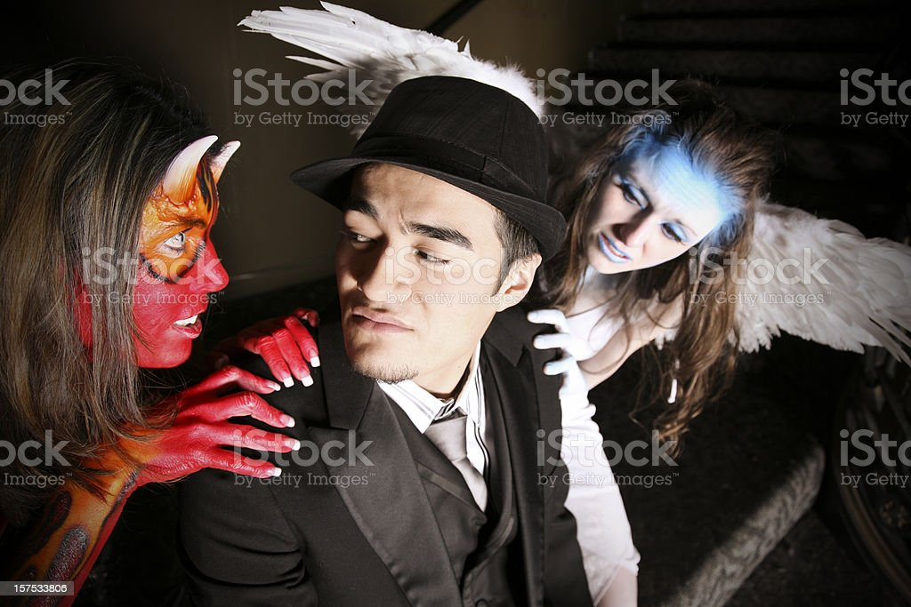 Man tempted by a she-devil and an angel royalty-free stock photo