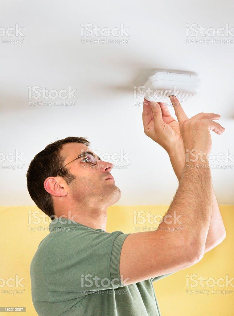 Man testing a smoke detector fire alarm stock photo