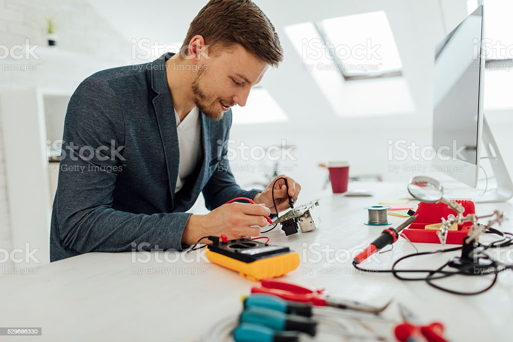 Man Testing circuit board in his office. stock photo