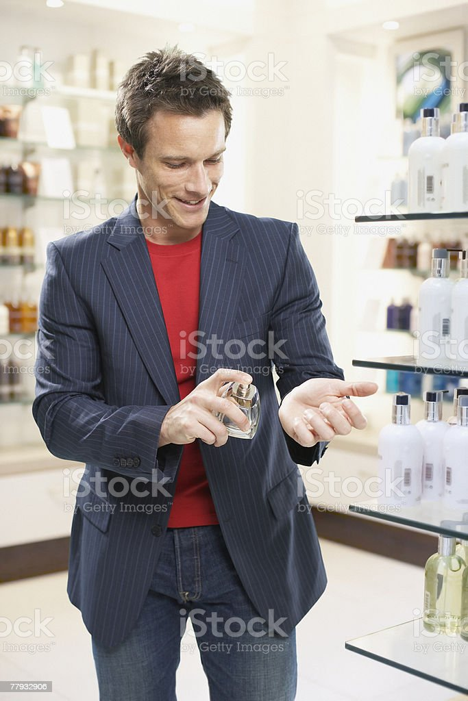 Man testing cologne in store stock photo