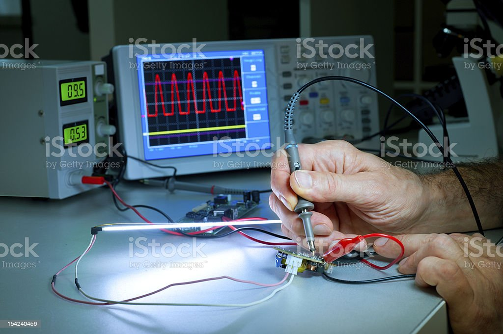 Man testing electronic equipment with machines nearby stock photo