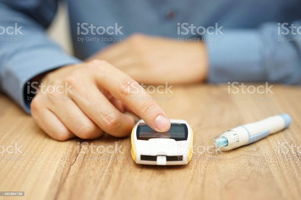 man testing glucose level with a digital glucometer, diabetes treatment stock photo