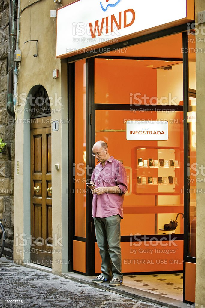 Man testing his mobile phone at the store entrance royalty-free stock photo