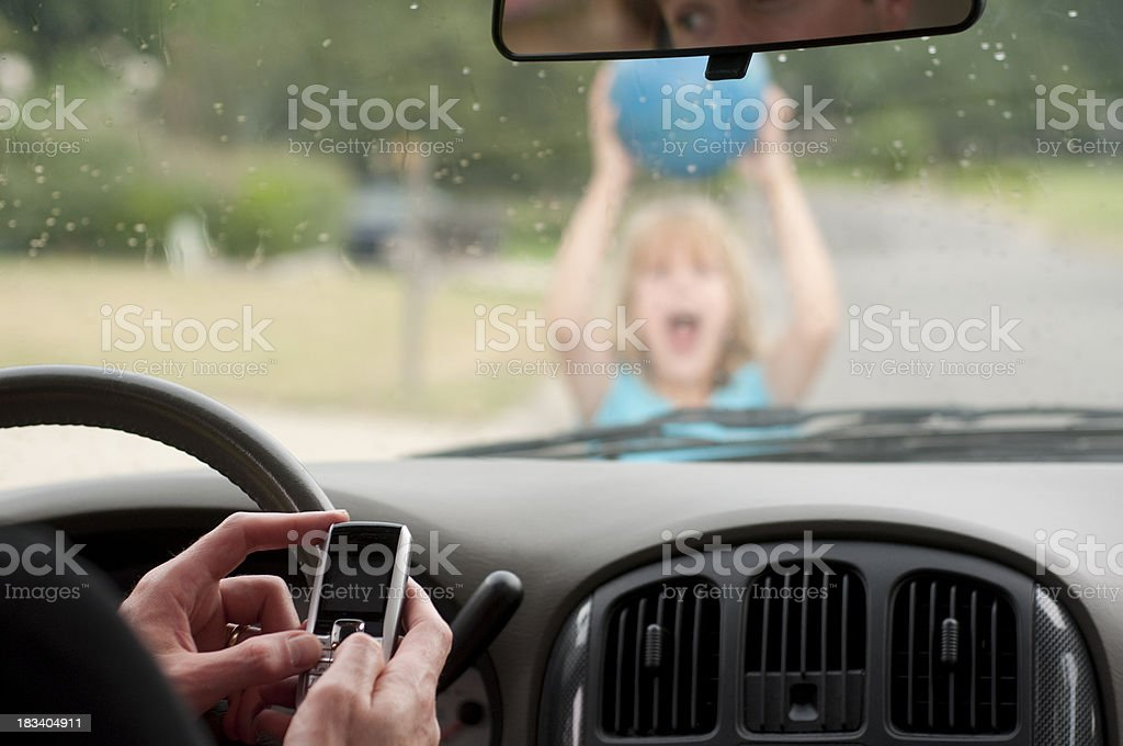 Man texting driving doesn't see girl running home in rain stock photo