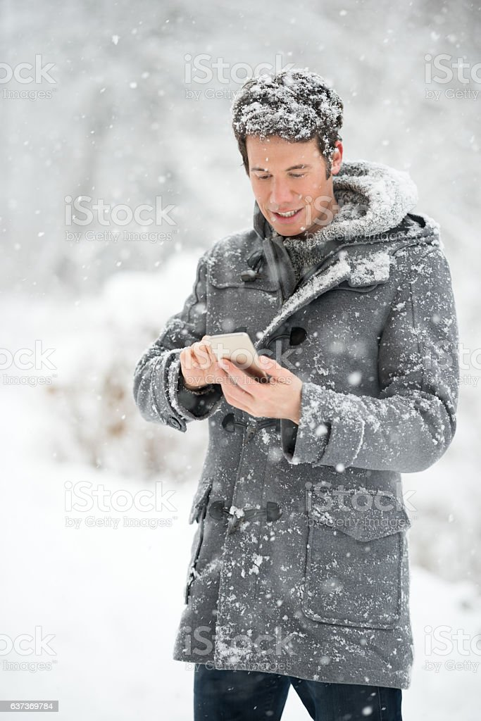 Man texting on his smart phone in a Snow Storm stock photo