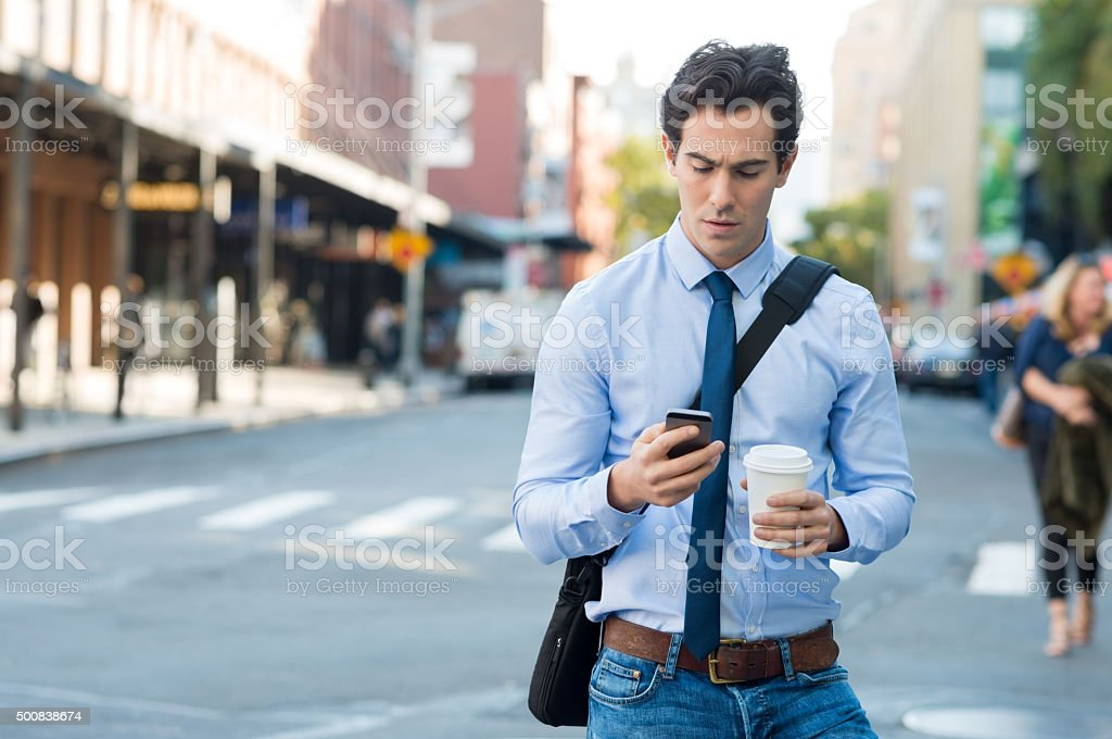 Businessman using smartphone and holding paper cup ina urban scene....