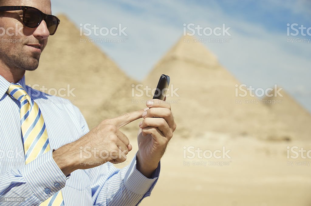 Man Texts on Smart Phone at Great Pyramids of Egypt royalty-free stock photo
