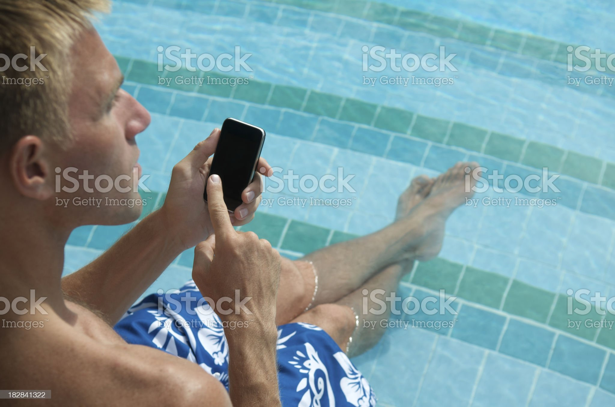 Man Texts on Smartphone Relaxing by Blue Swimming Pool royalty-free stock photo