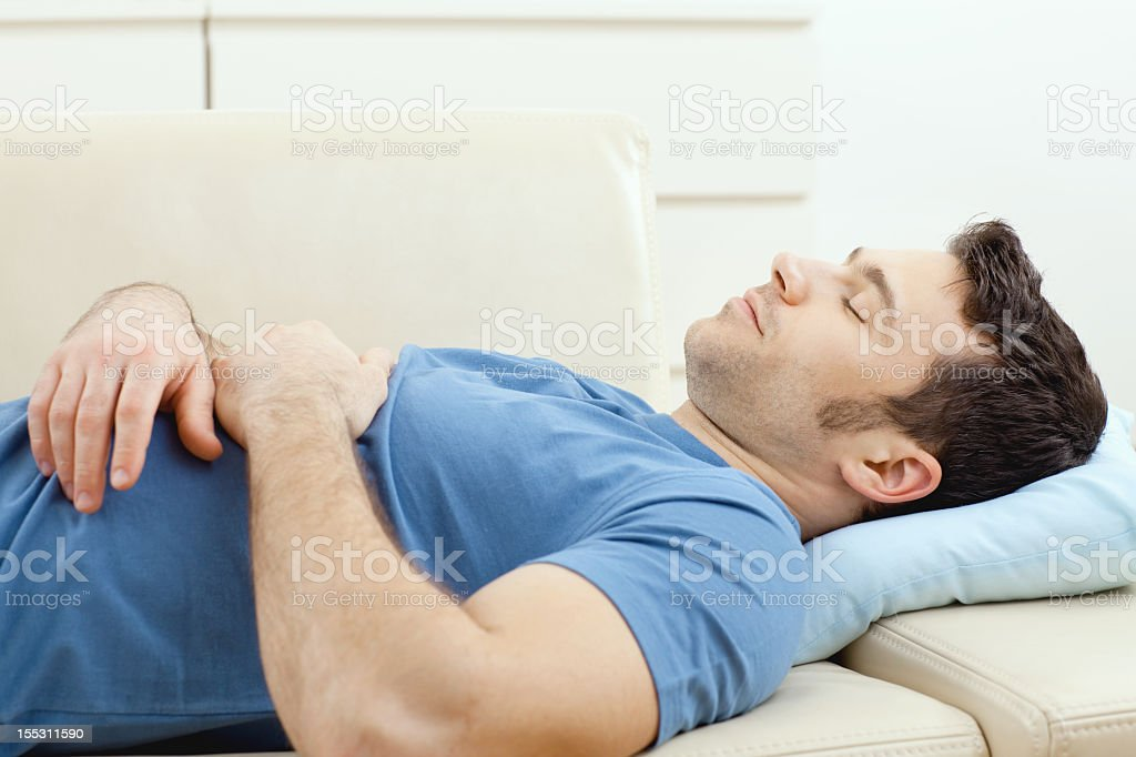 Man that is sleeping on the couch stock photo