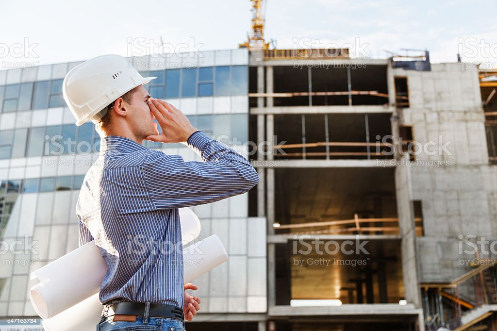 man the chief engineer at  construction site screams of danger. stock photo