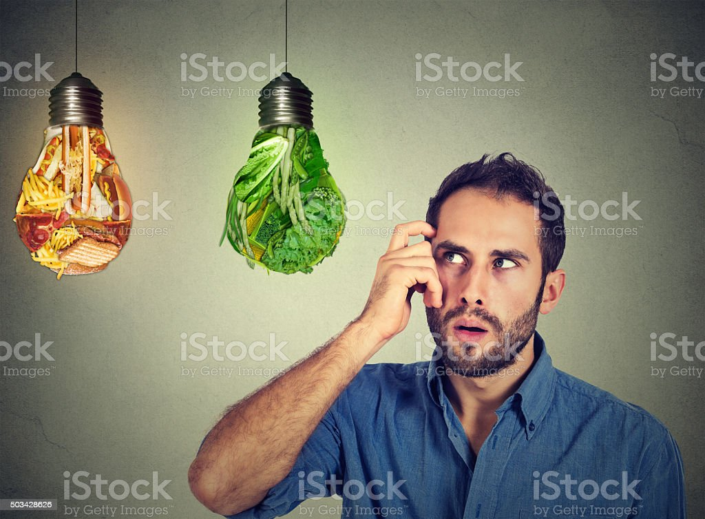 man thinking looking up at junk food green vegetables stock photo