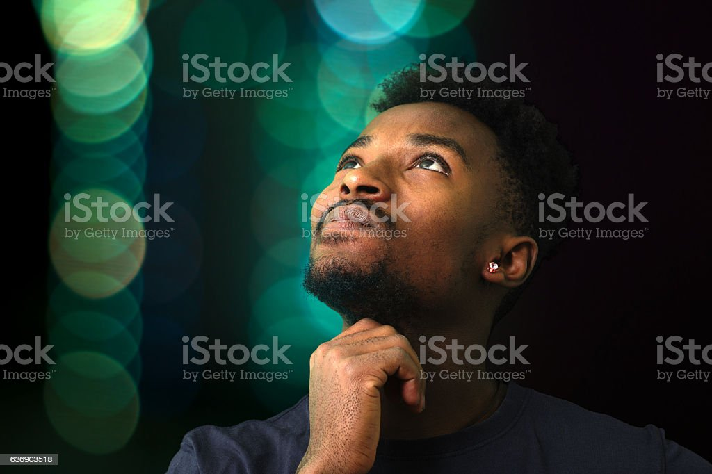 man thinking looking up on green lights background stock photo