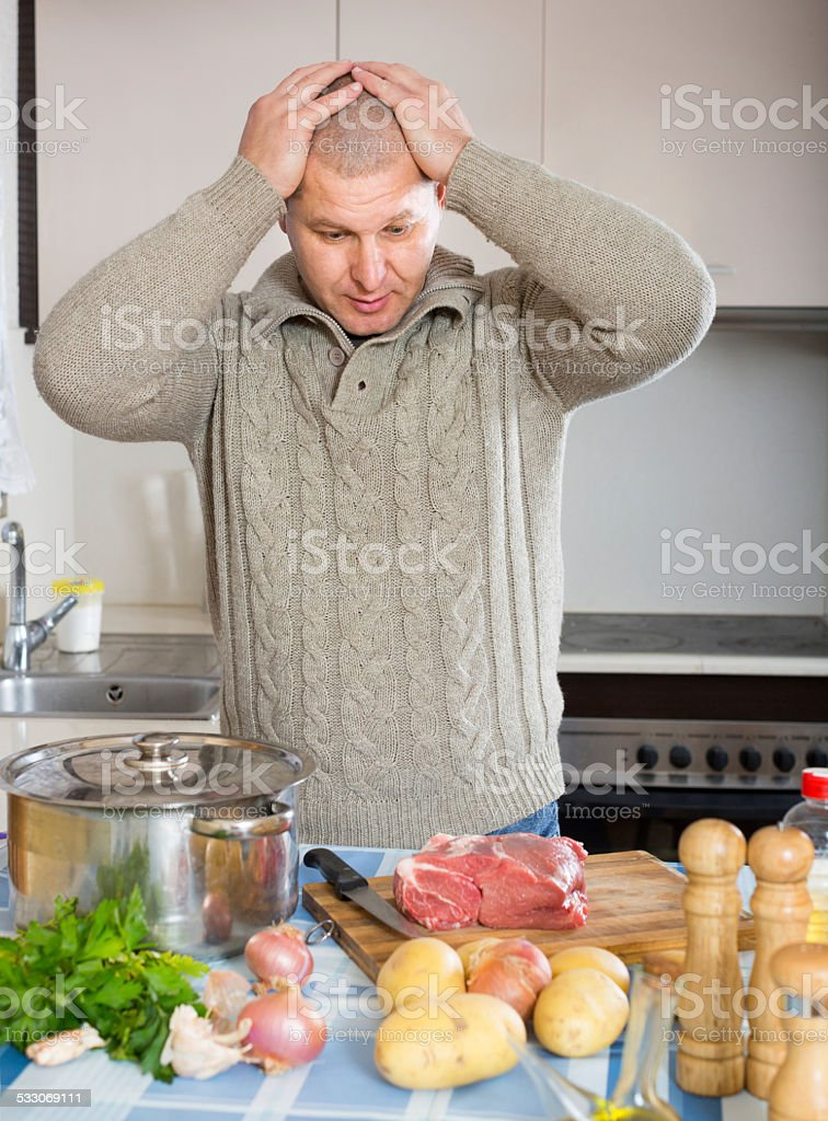 Man thinking what to cook for dinner stock photo