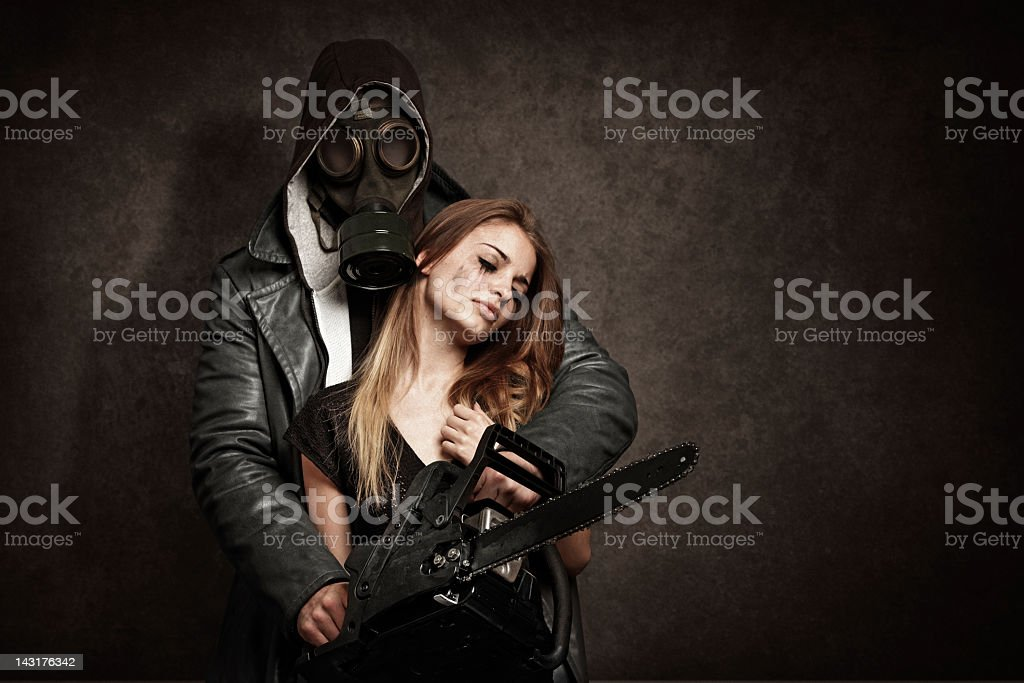 man threatening a young woman with chainsaw stock photo