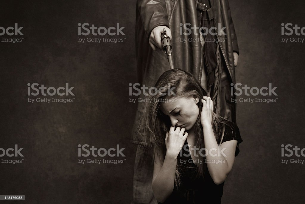man threatening a young woman with pistol stock photo