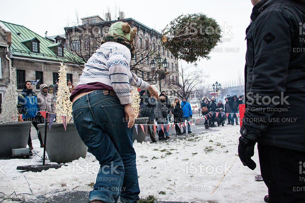 Man throwing a christmas tree in a competition stock photo