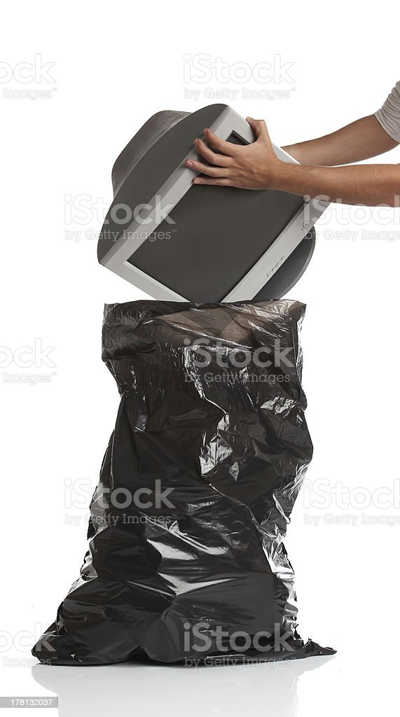 Man throwing a pc monitor in the garbage bag royalty-free stock photo
