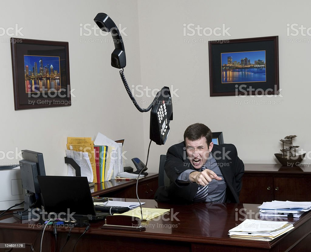 A man throwing a phone in a fit on his office royalty-free stock photo