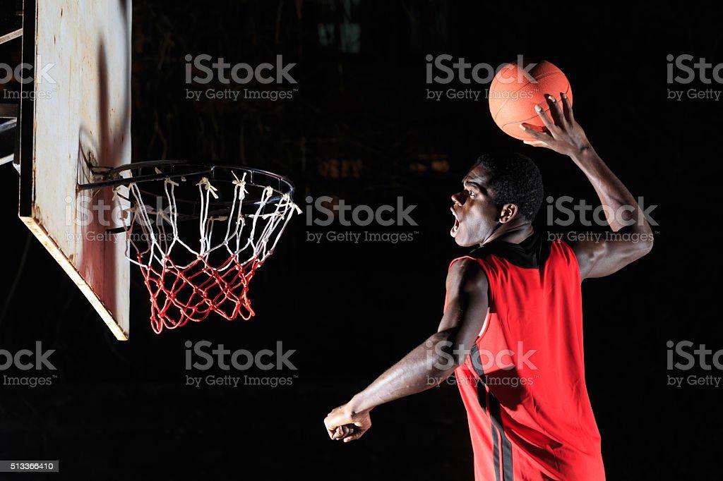 Man throwing basketball to makes slam dunk stock photo